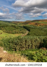 Near Levisham, North Yorkshire, England, UK: September 13, 2018: A train of the historic North Yorkshire Moors Railway passing Newtondale, seen from Skelton Tower in the Levisham Moor
