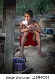 near pakbeng, laos - november 18, 2018: man smokes cigarette