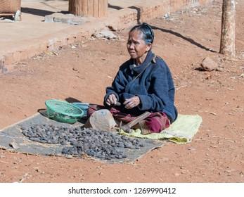 near pakse, laos - 11 24, 2018: woman sells nuts