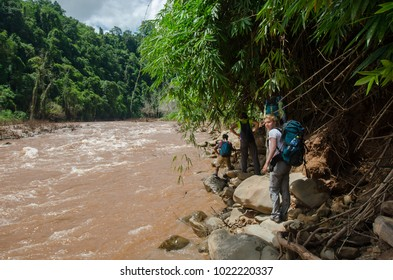NEAR PHONGSALY, LAOS - AUGUST, 2017 : Hiker walking along river stream located in North of Laos.