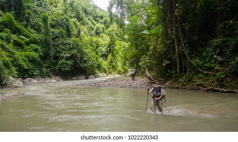 NEAR PHONGSALY, LAOS - AUGUST, 2017 : Hiker crossing a river during jungle trekking in North of Laos.