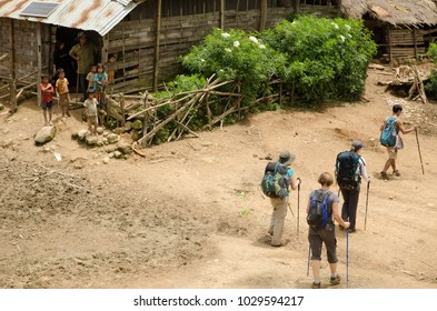 NEAR PHONGSALY, LAOS - AUGUST 21, 2017 : Hiker walking through Akha village located in North of Laos.