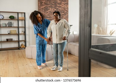 Near private nurse. Aged dark-skinned woman making first steps with crutches standing near private nurse