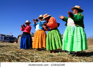 Near Puno, Lake Titicaca, Peru - August 9th 2012: Uro women in traditional clothes singing, dancing and clapping on one of the floating islands of the Uros