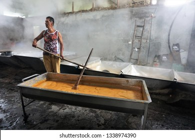 Near San Agustín, Huila Department, Colombia, February 21, 2019. Factory Worker attending to a Large Tub filled with a gooey Mass of liquid yellow Panela