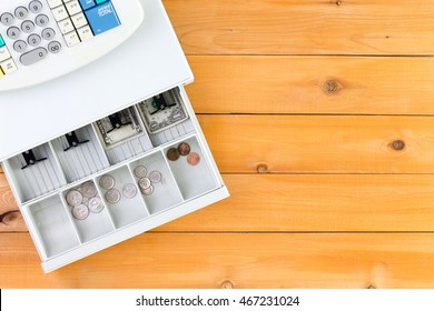 Nearly empty cash register drawer on table from top down view with copy space on wooden table