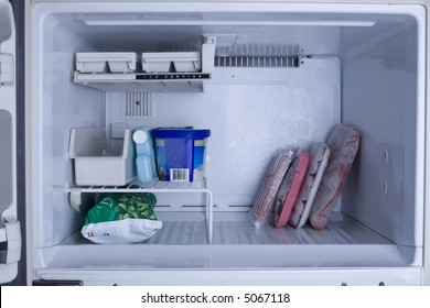 Nearly empty freezer with a cool blue tint
