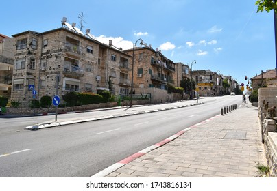 nearly empty street in Nakhalat Tsiyon in jerusalem israel during the corona virus covid pandemic lockdown with a clear sky and a few clouds in the background