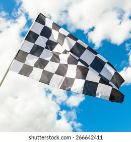 Neat checkered flag with cumulus clouds behind it