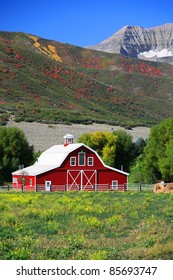A neat, clean red barn in a green field, with rolls of hay and hills in the background where the leaves are turning fall colors, and higher mountains behind.