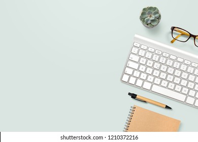 neat and clean, well organized home office workspace with technical gadgets, writing supplies, computer keyboard, glasses and a potted succulent plant on a mint background
