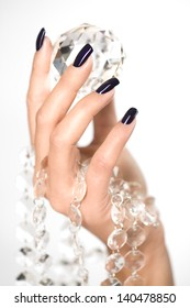 A neat female hand with black painted nails holding a large diamond
