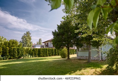 a neat little house in the garden with a lawn with grass and a green fence