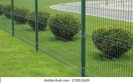 neat metal fence and bushes of a park zone in the city - Shutterstock ID 1720513639