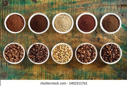 Neat still life of assorted varieties of ground coffee and medium, full and mild roasted beans in individual bowls on a rustic wood background viewed top down in two rows