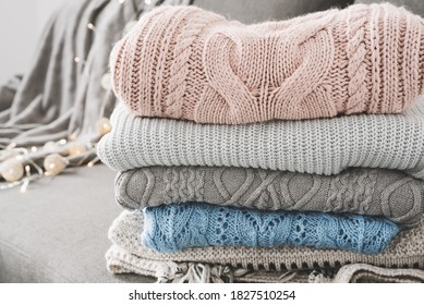 Neat and tidy pile of warm sweaters on gray sofa. Knitwear care. Knitted jumpers for cold fall and winter season