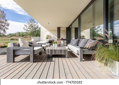Neat and tidy terrace with wooden garden furniture and plants on table