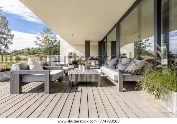 Аккуратная и аккуратная терраса с деревянной садовой мебелью и растениями на столе
