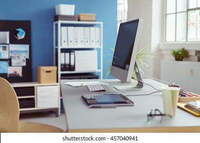 Neat workstation in an office with desktop computer, stylus and tablet with shelves of files and binders in the background
