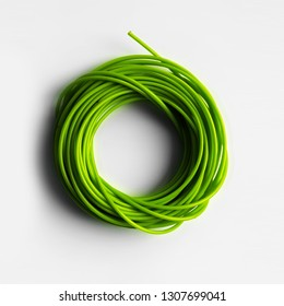 A neatly coiled green wire close up Isolated on a white background.