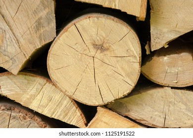Neatly stacked full frame wood beams and branches background texture patterns