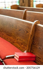 Neatly stacked hymnals await worshipers to the pews of this Christian church.