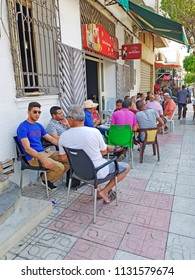 NEBEUL, TUNISIA - JUNE 21, 2018: Men drinking coffee on the street in the centre of Nabeul which is a coastal town in north-eastern Tunisia.