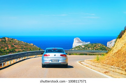 Nebida, Italy - September 13, 2017: Car on the road at Porto Corallo in Nebida, with the Mediterranean Sea, Carbonia-Iglesias, Sardinia, Italy