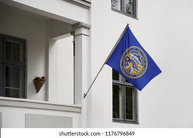 Nebraska flag. Nebraska state flag hanging on a pole in front of the house. State flag waving on a home displaying on a pole on a front door of a building. Flag raised at a full staff.