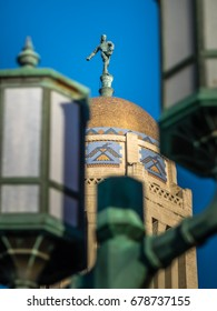 The Nebraska State Capitol in Lincoln is topped by a 20-foot bronze statue called The Sower, sowing seed. Here he is framed in the globes of a period-looking street lamp.