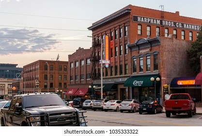Nebraska, USA - Aug 10, 2017: Brick commercial buildings with preserved historical aesthetic character along P Street in the Haymarket district, Lincoln City. Cars parked along this street.