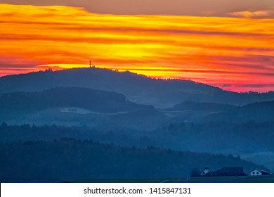 nebulous landscape oft the forest of odes with a farm, forest and hills  after sunset, Gemany, Europe