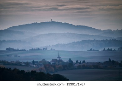 nebulous landscape with a village in the Forest of Odes after sunset, Germany, Europe