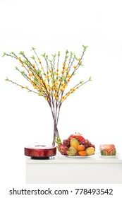 Necessary attributes for celebrating Tet holiday: glass vase with ochna tree branches, plate with ripe fruits, colorful decorations, isolated on white background