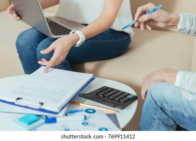 Necessary document. Clever responsible financial advisor feeling confident while sitting on a sofa with a modern laptop on her knees and pointing to the necessary documents