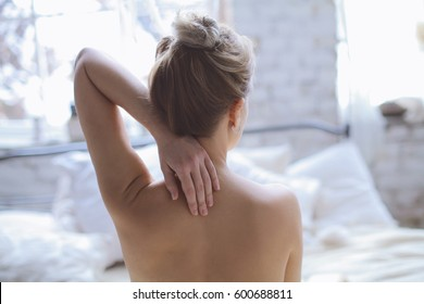 The neck and elegant tender hand of Young beautiful Girl in romantic boho bedroom interior in morning. Blond sexy naked female Boudoir photo sitting with her back to camera in front of large window