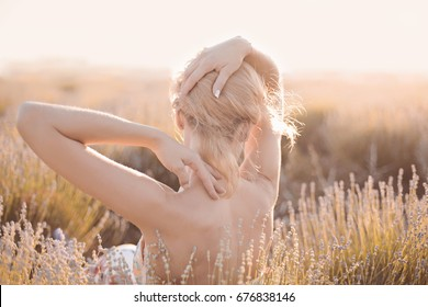 The neck and elegant tender hand of Young beautiful blonde Girl on lavender field in golden sunset light. Romantic Bare back woman take sun bath on floral field having vacations in Provence France
