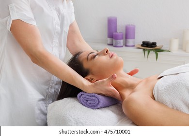 Neck massage in spa. Female beautician doctor with patient in wellness center. Professional cosmetologist make procedure to beautiful indian girl in cosmetology cabinet or beauty parlor.