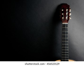 Neck of an old acoustic guitar on a black background (with copy space)