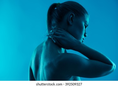 Neck pain. Close-up of young woman massaging her neck and back over blue background.