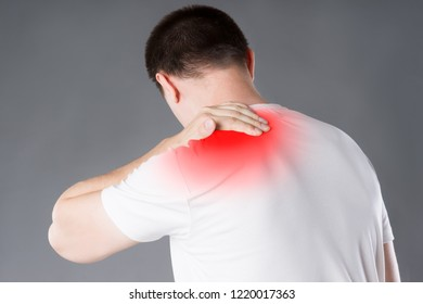 Neck pain, man suffering from backache on gray background, painful area highlighted in red
