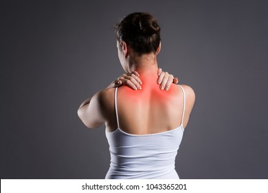 Neck pain, woman with backache on gray background, studio shot