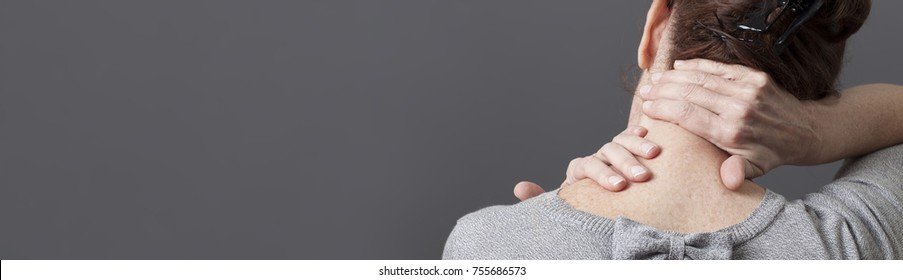 neck and shoulder gestures for releasing tension in back for middle aged woman, grey long panorama