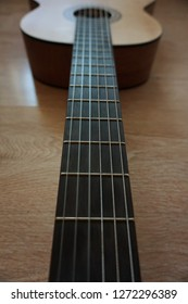 The neck of a six-stringed guitar with stringed strings