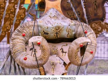 Neck of souvenir kobyz (ancient shaman's instrument) decorated with moufflon horns, wolf skin & symbols of shanyrak (sacred top of yurt) & petroglyphic drawings. Closeup. Selective focus