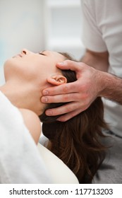Neck of a woman being manipulating by a therapist in a room