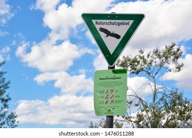 Neckarhausen, Germany - August 2019: Green sign with eagle and sign with behavior rules for German Nature Reserve, a category of protected area within Germany's Federal Nature Conservation Act