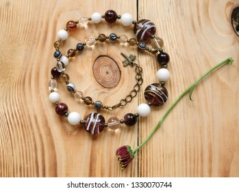 Necklace of burgundy glass Murano beads and chrysanthemum flowers on a wooden table, cosmic arrangement with women's bijouterie.