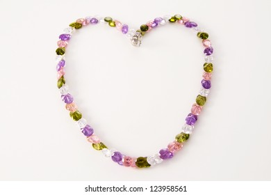 necklace of colored stones  in the shape of heart on a light background