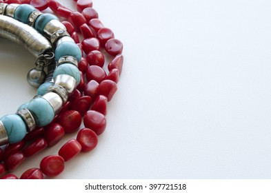 a necklace of coral and turquoise bracelet on a light background